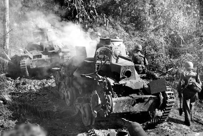 The smoking hulks of Japanese tanks, knocked out by the superior firepower of American Sherman tanks, smolder along a trail on the island.