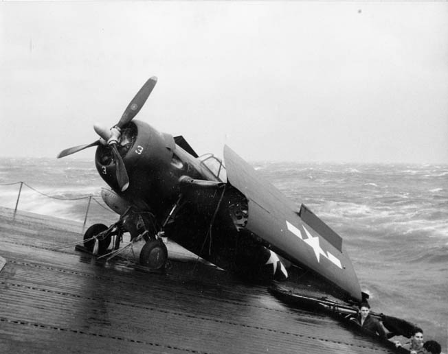 A U.S. Navy FM-2 Wildcat fighter plane hangs off the deck of the escort carrier USS Anzio. Having broken its moorings, the plane was nearly tossed overboard in the raging seas during Typhoon Cobra.