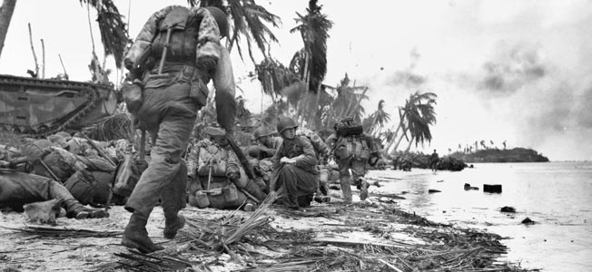 Marines pause on one of the invasion beaches on Guam in July 1944. An amphibious tracked vehicle is seen at left, while soldiers take up positions and prepare to advance inland.