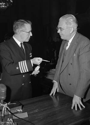 Captain L.F. Safford, chief of the Naval Intelligence section during the time of Pearl Harbor and a hearing witness, confers with Senator Homer Ferguson after a session.