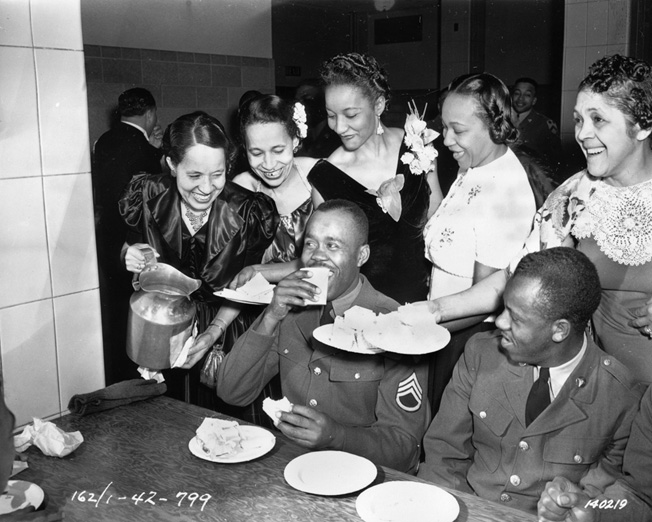 Black USO hostesses serve African American soldiers of the 2nd Cavalry Division at Camp Funston, Kansas. Because of segregation, the USO had to provide separate facilities for black and white troops.