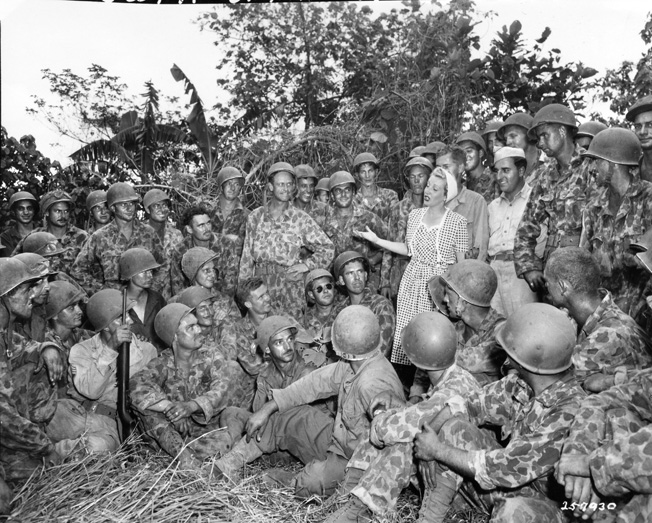 Songstress Martha Tilton, a vocalist with Benny Goodman's band and a member of the Jack Benny Troupe, entertains a rapt audience of soldiers of the 222nd Field Artillery Battalion on New Britain, July 1944. USO performers often risked their lives to bring smiles and a touch of home to troops stationed around the globe.