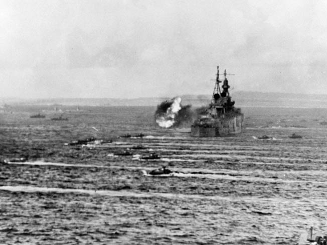 Landing craft churn past the heavy cruiser USS Indianapolis as the ship fires its big 8-inch guns in support of the landings on Saipan in the Marianas on June 15, 1944.
