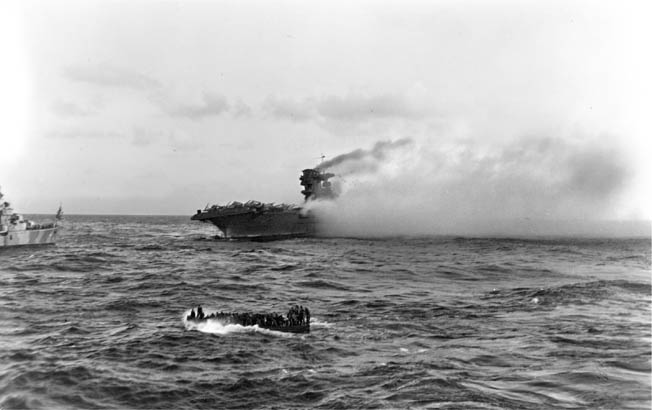 The USS Lexington burns furiously as crewmen abandon ship during the Battle of the Coral Sea. Although the Lexington was lost during the battle, the Japanese invasion force headed for New Guinea was turned back.