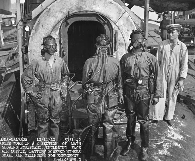Navy salvage personnel equipped with face masks, air supply, and battery-powered miner's lights come off their shift aboard Oklahoma, December 1942. While initial plans were made to salvage the ship, the Oklahoma was decommissioned in 1944.