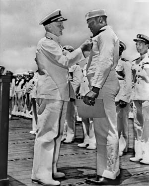 Admiral Chester W. Nimitz, the U.S. Navy commander in chief in the Pacific, pins the Navy Cross on Seaman Dorie Miller during a ceremony at Pearl Harbor on May 27, 1942.