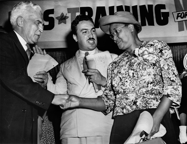 Paul V. McNutt, chairman of the War Manpower commission, shakes hands with Mrs. Connery Miller, mother of Dorie Miller. Reverend Adam Clayton Powell, Jr., looks on during a rally of the Negro Labor Victory Committee held in Harlem.