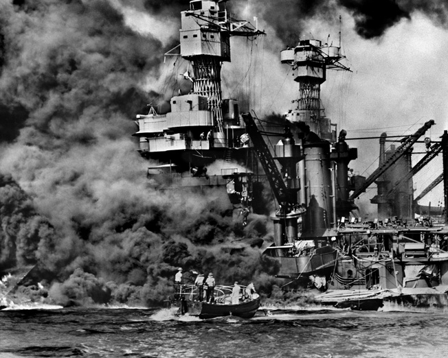 The battleship USS West Virginia settles on an even keel to the bottom of Pearl Harbor after sustaining multiple torpedo hits from Japanese planes on December 7, 1941. Rescuers in a motor launch pull a sailor from the water as smoke billows.