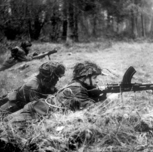 Canadian paratroopers man a position at the edge of a forest shortly after landing. The soldier in the foreground is armed with a Bren gun.