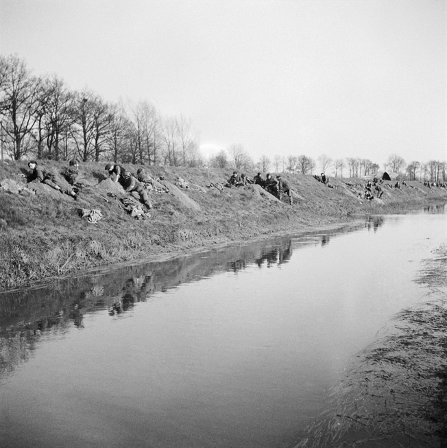 "British glider troops of the Royal Ulster Rifles dig in on the banks of the Issel River after landing. The RUR were ""old hands"" at such operations, having successfully knocked-out the Merville Battery in Normandy on D-Day."