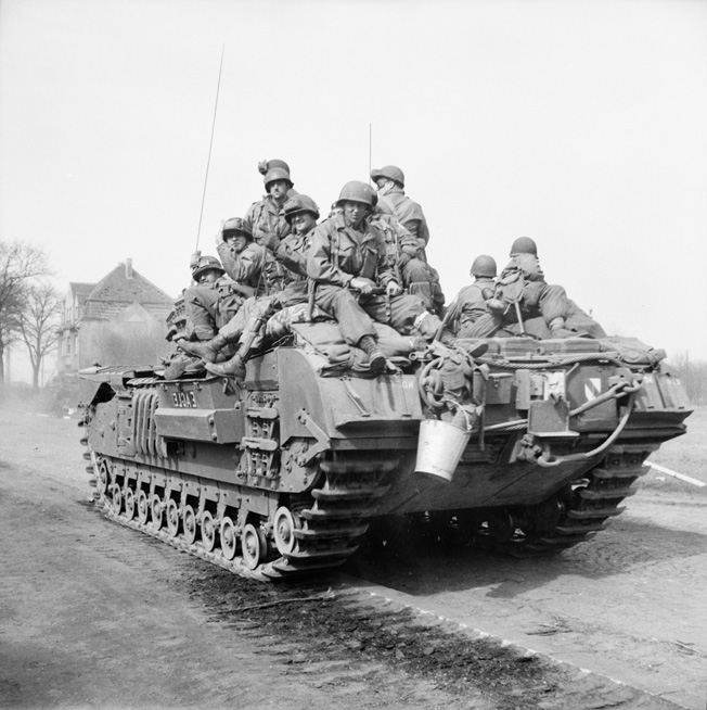 A Churchill tank of the 6th Guards Tank Brigade carries paratroopers of the American 17th Airborne Division through Dorsten, Germany, March 29.