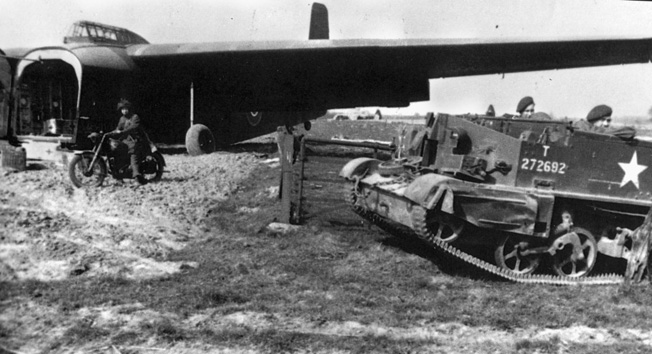 "A British Bren, or Universal, Carrier, probably belonging to the 12th Devons, on LZ ""P"", has just emerged from the Hamilcar glider in the background."