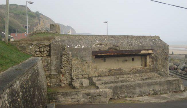 The same pillbox today; the shell mark above the embrasure is still visible, but the side wall has been demolished. The cliffs of Charlie Beach can be seen in the distance.
