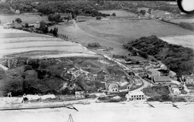 An aerial photograph taken by a Royal Air Force reconnaissance plane shows the Vierville Draw on June 30, 1943, almost a year before D-Day. The houses around the U-bend in the road were demolished by the Germans and replaced by strongpoints, pillboxes, and Widerstandsnests.