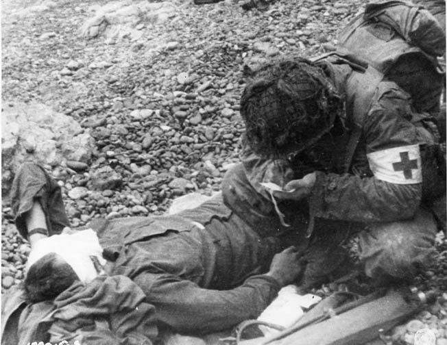 An American medic fills out a casualty report on a wounded soldier at Omaha Beach.