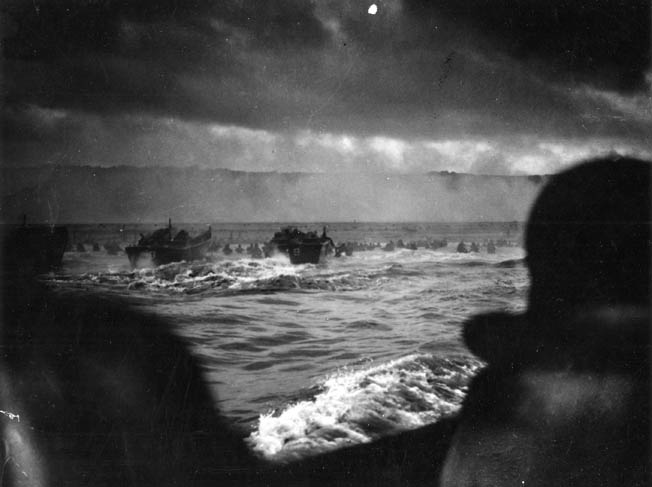 Landing Craft Vehicle, Personnel (LCVPs) churn through the rough surf toward the obstacles on smoke-shrouded Omaha Beach. The Germans had prepared a perfect killing ground for the American forces.