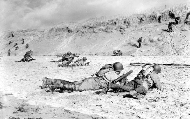 American bazooka teams train in England for combat on Omaha Beach. Although considerably smaller, the sand berm in the distance gave troops an idea what they would encounter on D-Day.