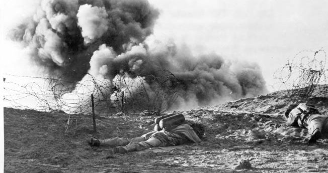 Two soldiers, one armed with a flamethrower, brace themselves against the force of a TNT blast that destroyed a section of concertina wire during training in England.