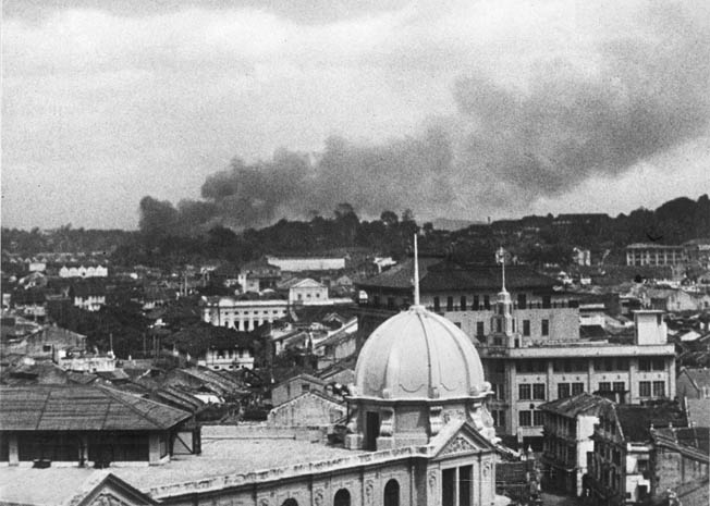 A view from Raffles Square shows a pall of smoke drifting over Singapore after a Japanese air raid on the capital.