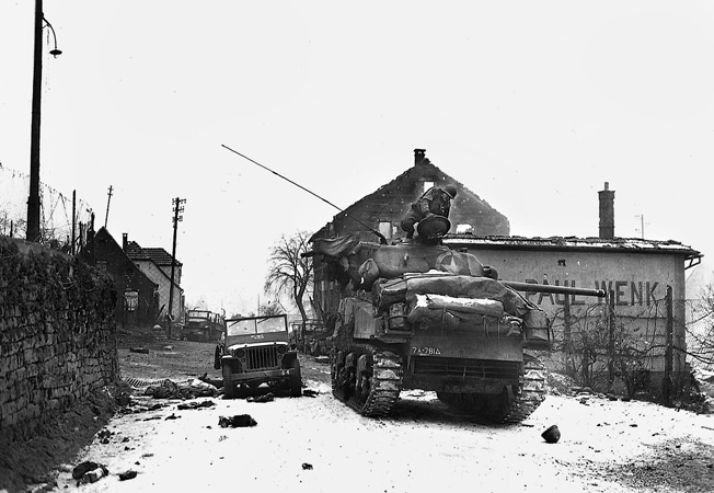 An M4 Sherman tank of the 781st Tank Battalion, in support of the 100th Division outside of Wingen-sur-Moder, France, January 6, 1945. A GI helmet and knocked-out vehicles bear witness to the fierce fighting.