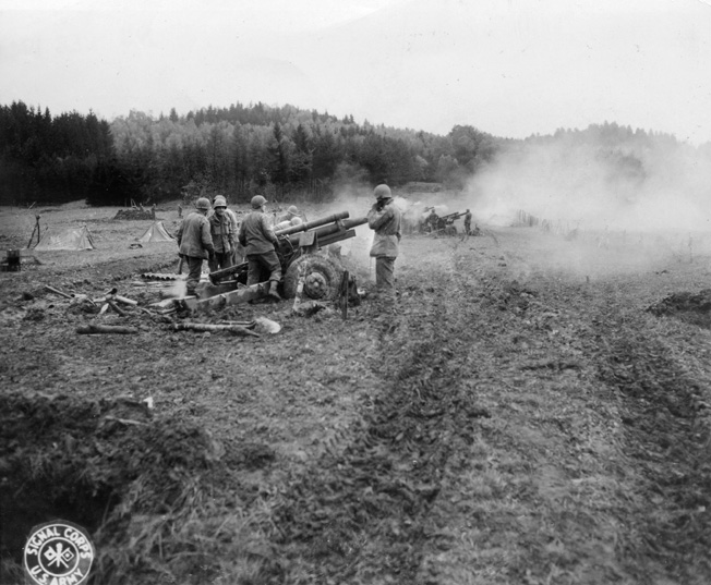 105mm howitzers of the 925th Field Artillery Battalion, 100th Division fire a barrage to stop a counter-attack in France.