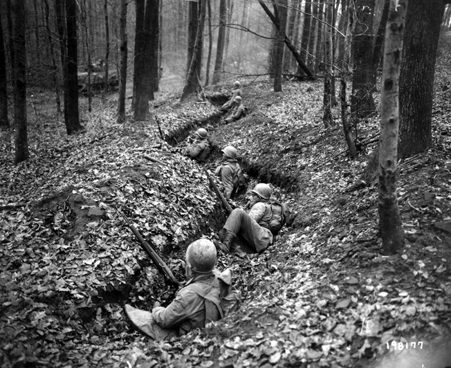 Men of the 399th watch from their trench line as an American tank rolls past on a forest road. By holding firm against the enemy's counterattacks and capturing Bitche in March 1945, the 100th Division earned praise from higher headquarters.