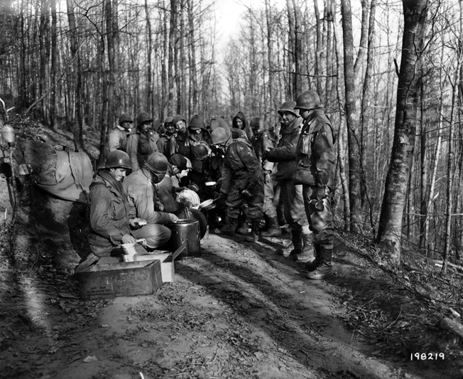 Christmas Eve dinner at the front: men of the 399th Regiment line up to receive hot chow—a rare treat.