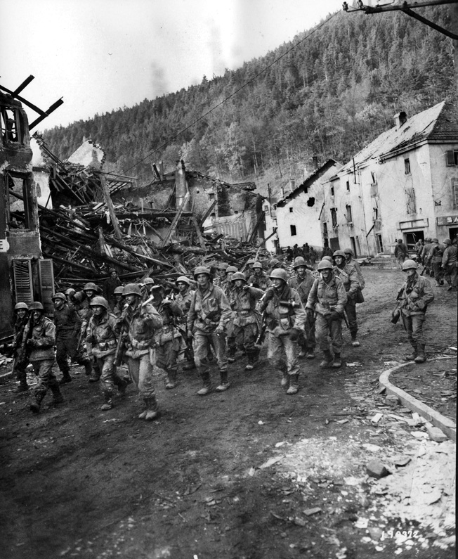 Elements of the 100th Division move through the ruins of Raon L'Etape in the Vosges Mountains area of northeastern France.