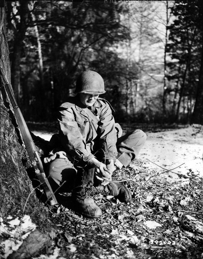 A 399th GI dries his feet and changes socks to avoid trench foot. Officers threatened to court-martial soldiers if they developed trench foot; it was a hollow threat.