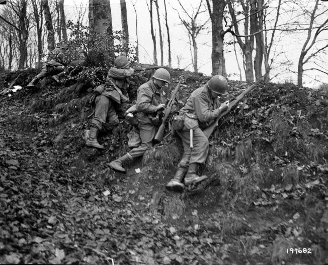 100th Infantry Division riflemen fire from behind a berm near Rosteig, France, several miles south of Lemberg, in early December 1944.