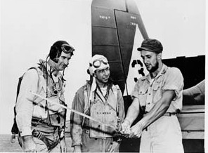 Lieutenant Vraciu shows off a captured Japanese officer's sword to fellow Navy pilots aboard a carrier after his return from behind enemy lines on Luzon. After his Navy fighter was downed by antiaircraft fire over the Philippines, Vraciu joined a band of guerrillas and participated in operations against the enemy.