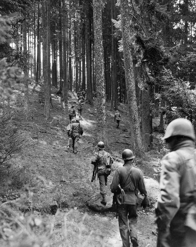 Troops of the 90th Infantry Division move through the woodlands of Czechoslovakia while probing German positions near the southern German-Czech border.