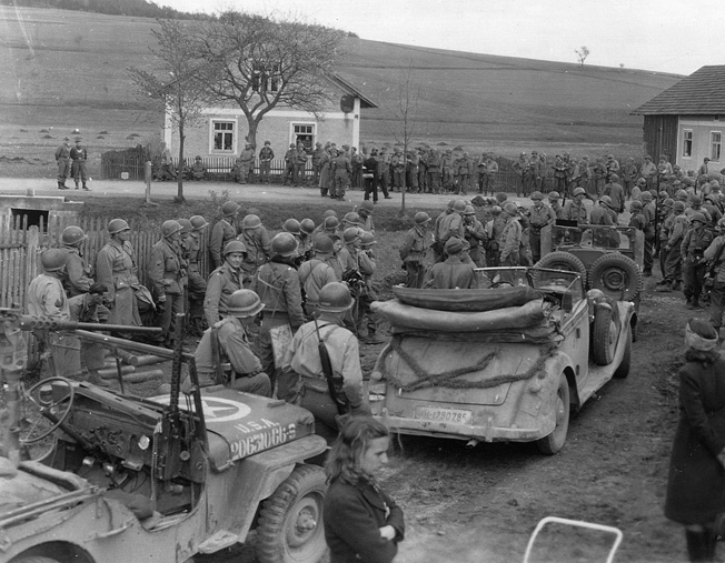 A crowd of 90th and 2nd Infantry Division troops gather as the German 11th Panzer Division makes its formal surrender in May 1945.