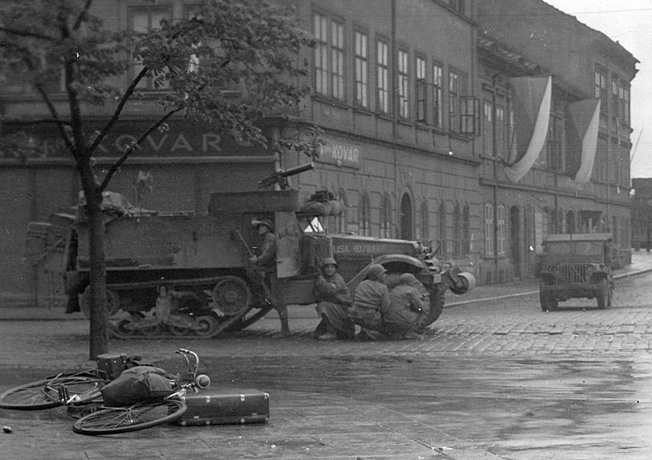 Rolling through a Czech city, U.S. infantrymen quickly take cover as their halftrack comes under the attack of Wehrmacht snipers.