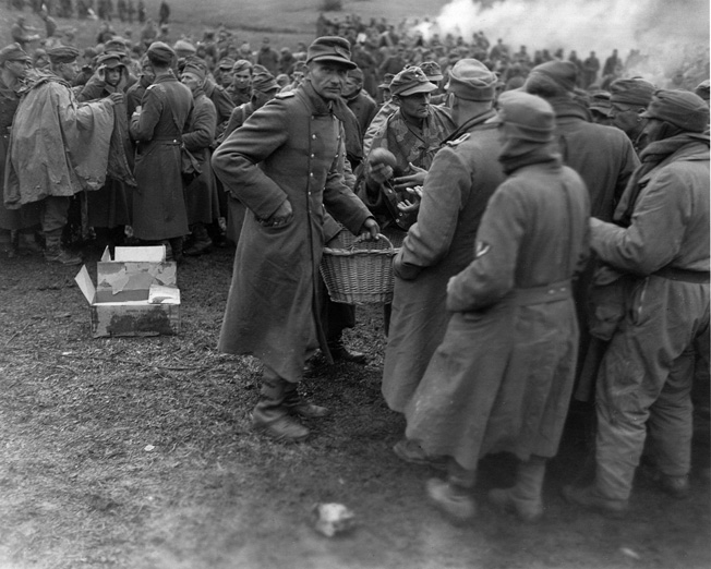 Shortly after a surrender to U.S. forces, German officers hand out rations of bread to hungry soldiers.