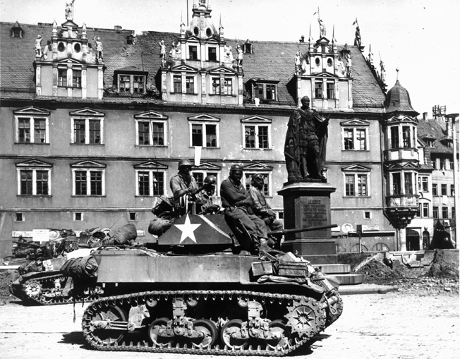 Sitting atop their Stuart light tanks, soldiers of Patton's Panthers wait for orders to enter the town of Coburg, Germany, to clean out pockets of stubborn German resistance.