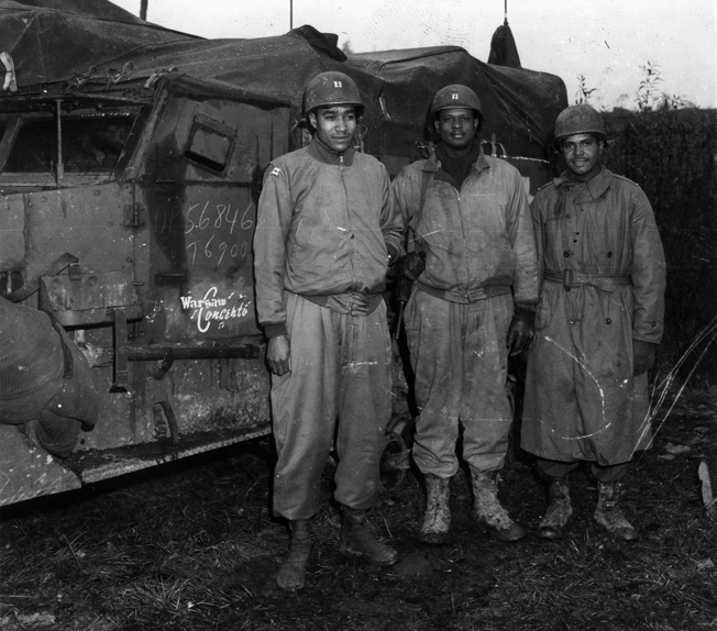 Field officers of the 761st Tank Battalion pause during preparations for upcoming action near Nancy, France, on November 5, 1944. The officers are (left to right) Captain Ivan Harrison, Captain Irvin McHenry, and 2nd Lieutenant James Lightfoot.