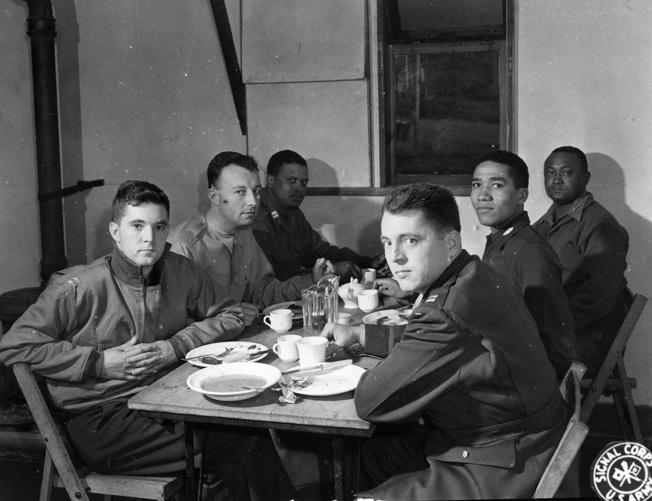 In September 1944, company commanders of the 761st Tank Battalion gather around tables for lunch. The vast majority of officers who served in black units during the war were white.