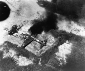 A Japanese bomber is slowly consumed by flames following a raid by American aircraft. As the war in the Pacific progressed, American bombing raids grew in strength and number and often caught Japanese aircraft on the ground.