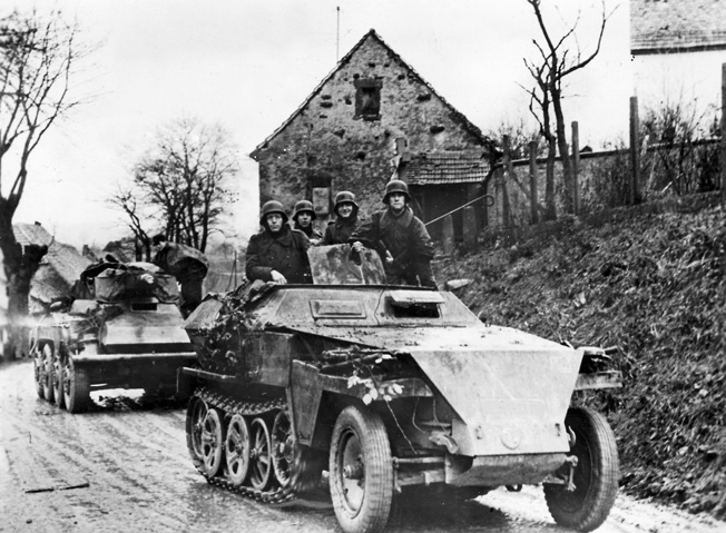 In October 1944, a German Schutzenpanzer half-track moves toward the fighting on the Western Front in company with a light tank.