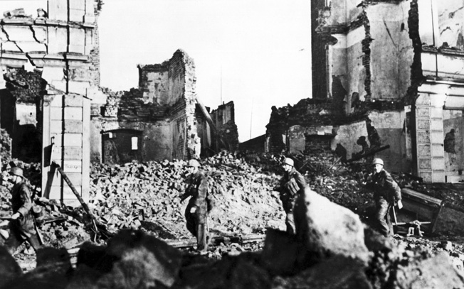 Elite German paratroopers, or fallschirmjager, were among the defenders of Aachen. Here, three of these soldiers are seen scrambling through the rubble of a destroyed building in the city as they move to new defensive positions.