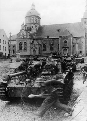 German tanks and panzergrenadiers assemble in the town square of Aachen prior to mounting a counterattack against advancing American troops. A Volkssturm panzergrenadier is seen sprinting past a Sturmschutze assault gun with a Panzerfaust antitank weapon in hand.