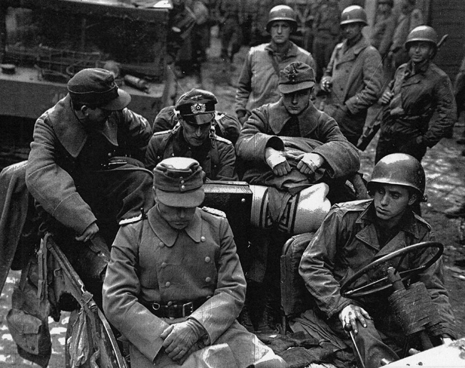 German officers, surrounded by their American captors, appear despondent after the fall of Aachen.
