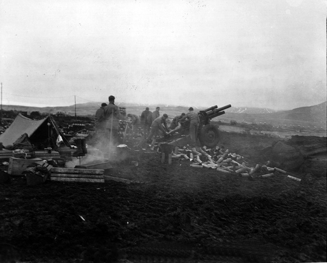 About 200 yards inland from a stormy beach on Attu, U.S. soldiers fire a 105mm howitzer against Japanese positions at Massacre Bay in May 1943.