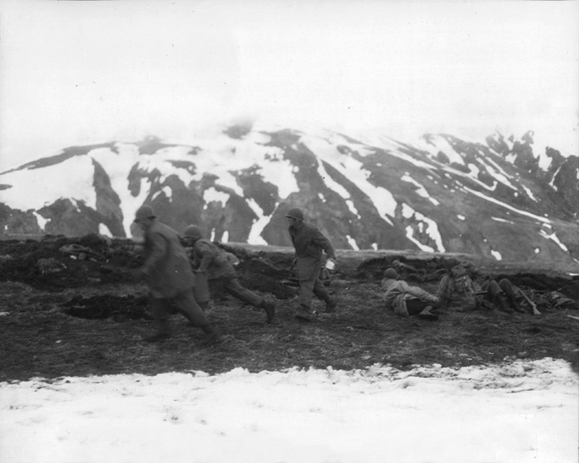 U.S. soldiers hustle hot food to troops manning the perimeter on Attu in May 1943. Hot food was considered a luxury in most combat areas.