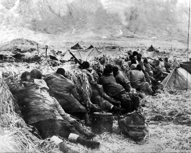 Clad in waterproof clothing to ward off the wet chill of the Aleutians, American troops take cover and scan for enemy snipers located in the mountains above Massacre Bay on Attu Island.