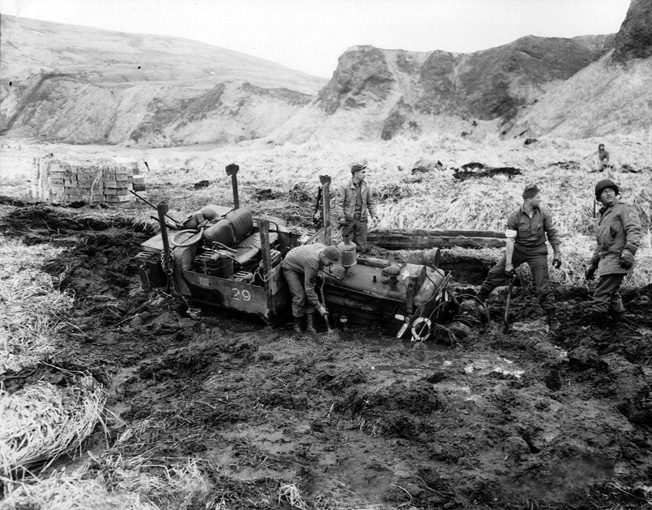 Bogged down on a muddy trail in the Aleutians, a tractor meant to move earth has become its prisoner. The sound of approaching aircraft has grabbed the attention of the soldiers attempting to reclaim the equipment.