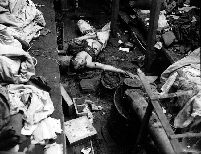 The body of a Japanese soldier who fought to the death lies sprawled on the floor of his bunker at Hoitz Bay on the island of Attu. The soldier had been previously wounded as evidenced by old bandages.