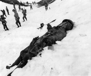 Lying dead in the snow, the body of a Japanese soldier killed in action at Hoitz Bay on Attu awaits a burial detail.