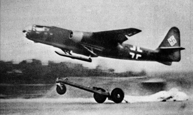 An early version of the Arado Ar-234 jet bomber is assisted by a trolley during takeoff. The apparatus fell away as the plane became airborne. Note the skids that were utilized for landing purposes.